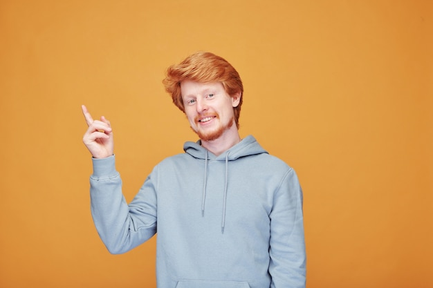 Happy young man in blue hoodie pointing upwards while showing you something or expressing satisfaction over yellow wall