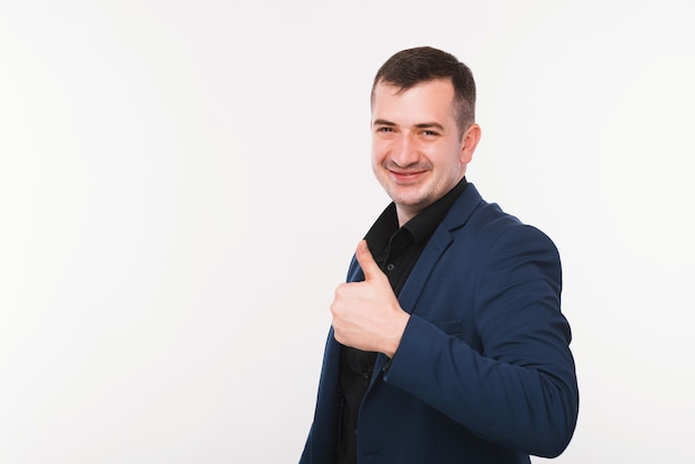 Happy young man in blue suit is showing thumb up and smiling near white wall.