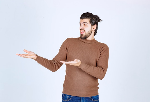 Un giovane felice in maglione marrone in piedi e mostrando qualcosa con le mani.