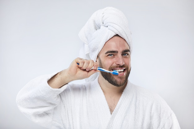 幸せな若い男の歯を磨く