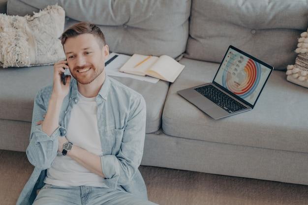Счастливый молодой человек звонит семье, чтобы сообщить о повышении в своей компании после представления успешной идеи проекта, сидя на полу, опираясь на диван с открытым ноутбуком, показывая графики