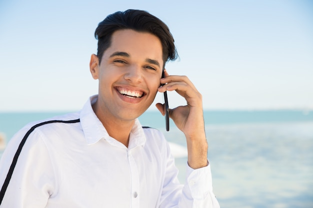 Happy young man calling on smartphone outdoors