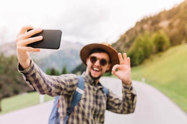 Счастливый молодой человек, несущий синий рюкзак, делая селфи с улыбкой и знаком хорошо, стоя на дороге