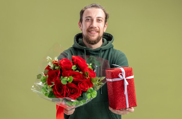 Happy young man in casual clothes with bouquet of red roses and present for his girlfriend looking at camera smiling cheerfully standing over green wall valentines day concept