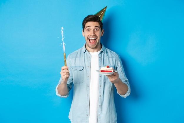 파티 모자를 쓰고 생일을 축하하는 행복한 청년, b-day 케이크를 들고 웃고, 파란 배경 위에 서서