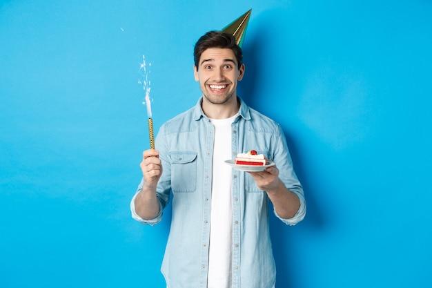 Felice giovane che festeggia il compleanno con un cappello da festa, tiene in mano una torta di compleanno e sorride, in piedi su sfondo blu