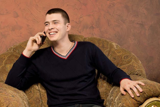 幸せな若い男が彼の携帯電話でおしゃべり
