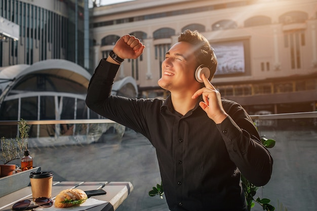 Happy young man cheering. he sits at table outside and wave with fists. guy enjoying listening to music. sun is shining.
