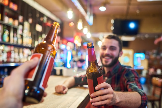 Happy young man clinking bottles with friend in bar