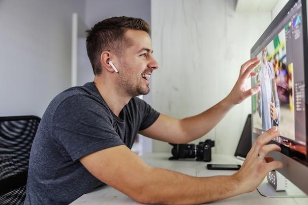 幸せな青年がインターネットヘッドフォンを介して同僚とコミュニケーションを取り、彼らはバーチャルリアリティプロジェクトと画面上の写真の3d効果について話します。写真、デザイン、プログラミング