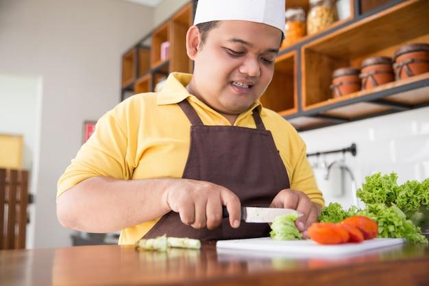 彼の食事を調理する幸せな若い男