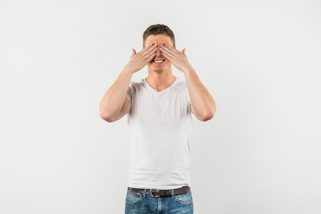 Happy young man covering his eyes with two hands against white background