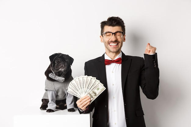 Happy young man and cute black dog standing in party costumes, pug owner holding money dollars and rejoicing, winning prize, white.