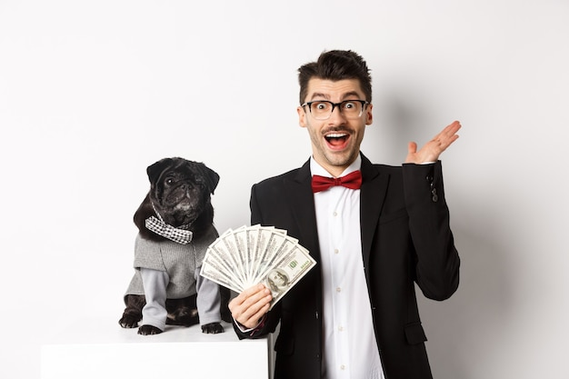 Felice giovane uomo e simpatico cane nero in piedi in costumi da festa, proprietario di un carlino che tiene in mano dollari di denaro, fissando la telecamera stupita, sfondo bianco