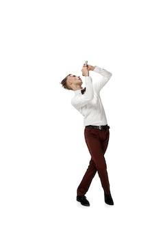 Felice giovane uomo che balla in abiti casual o completo, rifacendo mosse leggendarie di celebrità dalla storia della cultura