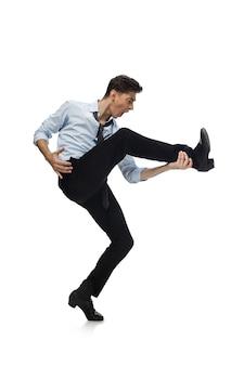 Счастливый молодой человек танцует в повседневной одежде или костюме, переделывая легендарные движения знаменитостей