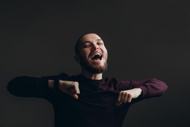 灰色の空間の上で踊って幸せな若い男。ひげでハゲ