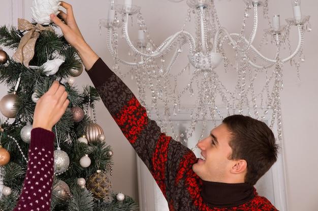 彼は飾りを上に置くためにストレッチしながら笑顔でクリスマスツリーを飾る幸せな若い男