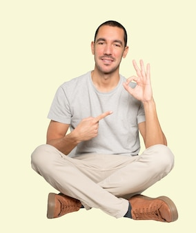 Счастливый молодой человек делает правильный жест