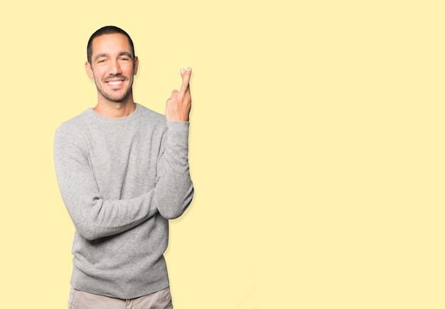 Happy young man doing a crossed fingers gesture