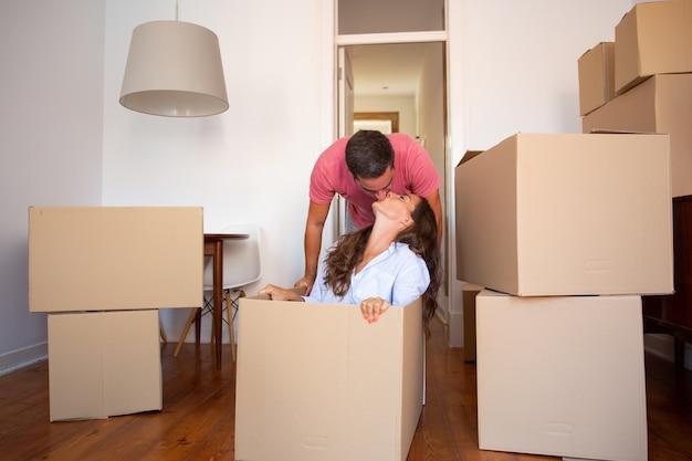 幸せな若い男は彼のガールフレンドと一緒に箱をドラッグして彼女にキスします