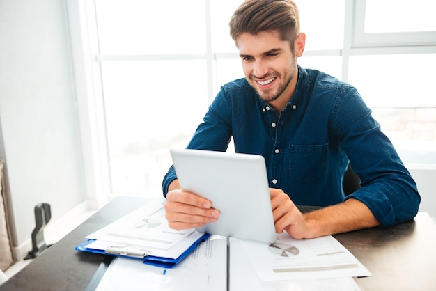 Happy young man dressed in blue shirt sitting at home near documents while holding tablet in hands and smiling