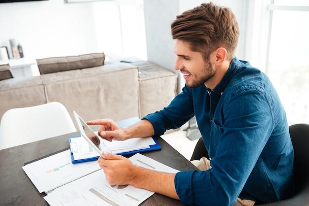 Счастливый молодой человек, одетый в синюю рубашку, сидит дома возле документов и анализирует финансы, держа планшет в руках и улыбаясь