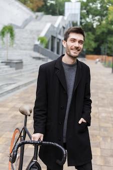 Счастливый молодой человек, одетый в пальто, гуляет с велосипедом по улице