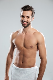 Happy young man dressed in towel standing isolated