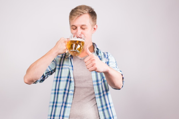 ビール ジョッキを飲んで親指を立てる幸せな若い男