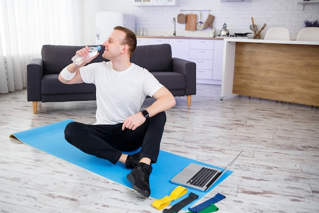 Happy young man drinks water after training online. doing sports at home, healthy lifestyle