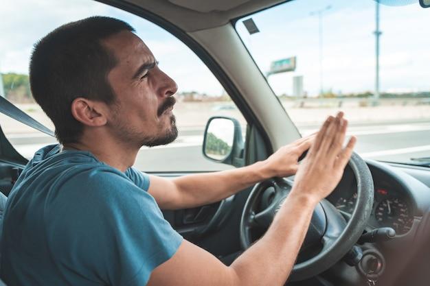 車を運転して踊ったり歌ったりする幸せな若い男楽しい旅行交通機関と車両のコンセプト
