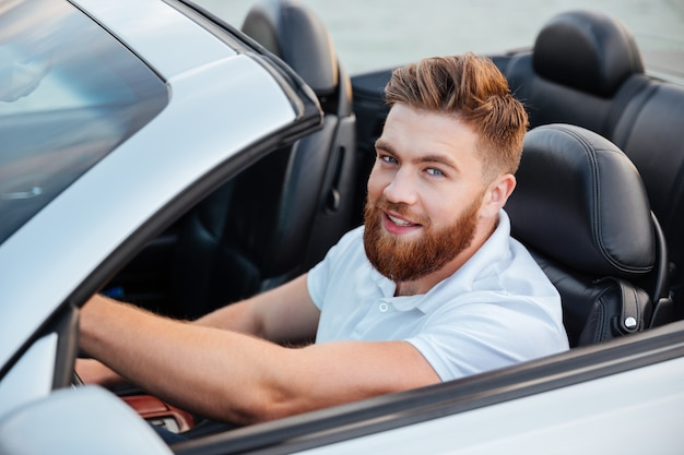 Happy young man driving cabriolet and looking at front