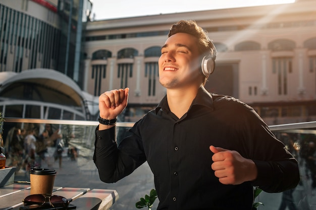 Happy young man enjoys listening to music. he dance at table outside. guy wave with hands. it is sunny outside.