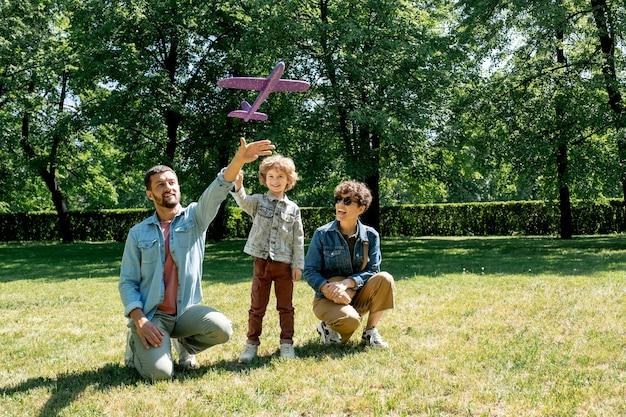 Счастливый молодой человек летит на игрушечном самолетике во время игры со своим очаровательным маленьким сыном на зеленой лужайке и его смеющейся женой, сидящей на корточках рядом