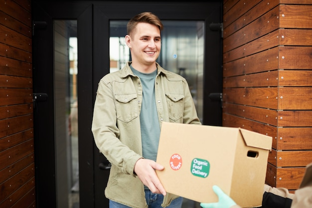 Happy young man getting the box with food from courier outdoors