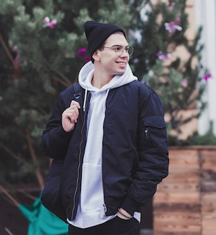 Happy young man in glasses holding his backpack