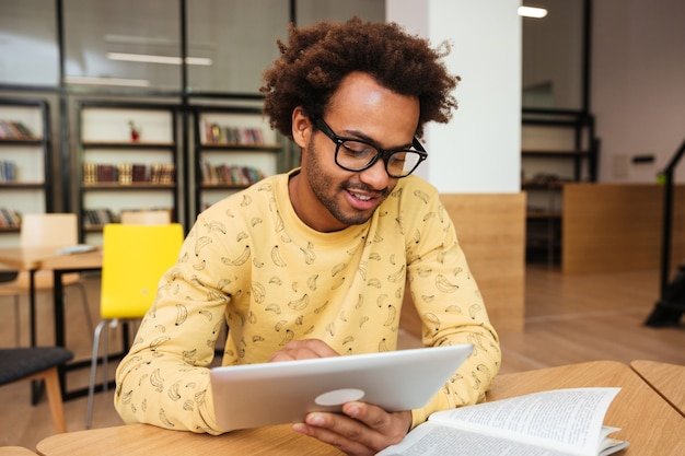 Happy young man in glasses learning and using tablet in library