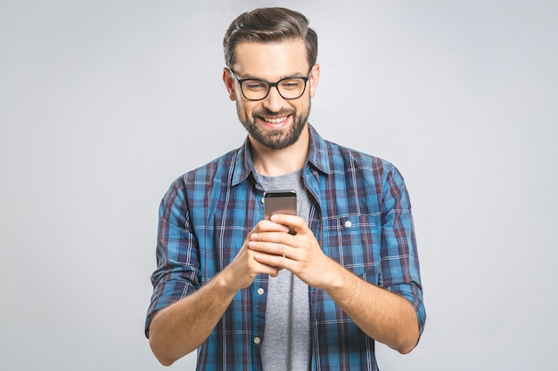 Happy young man in glasses typing sms on gray wall
