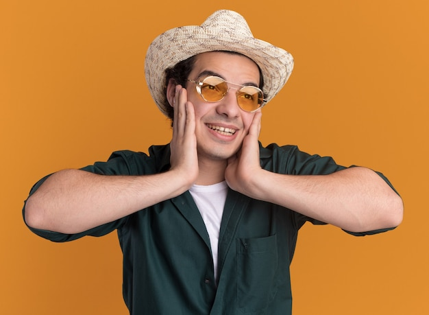Felice giovane uomo in camicia verde e cappello estivo con gli occhiali che osserva da parte con il sorriso sul viso in piedi sopra la parete arancione