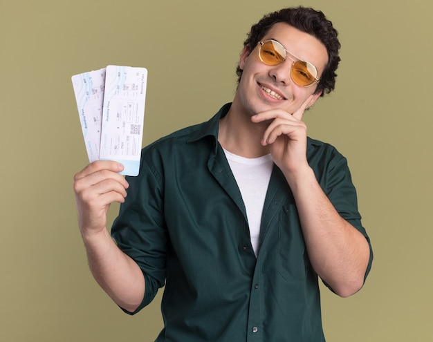 Happy young man in green shirt wearing glasses holding air tickets looking at front with smile on face standing over green wall