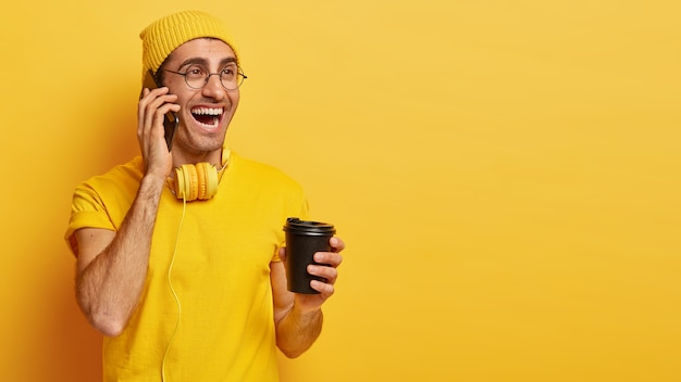 Happy young man has good talk via cell phone, holds takeaway coffee, enjoys drink, dressed in casual t shirt and hat