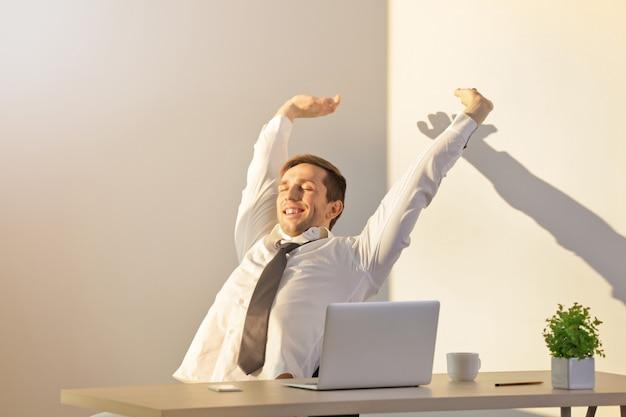 明るい部屋の職場で短い休息を持っている幸せな若い男