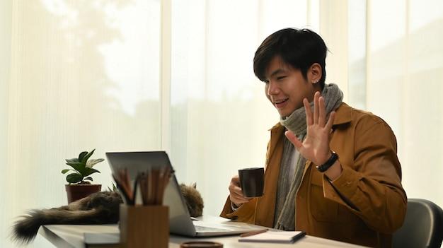 집에 앉아 노트북 컴퓨터로 친구들과 영상 통화를 하는 행복한 청년.