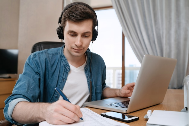 Happy young man in headphones sitting at desk in home office, writting on paper