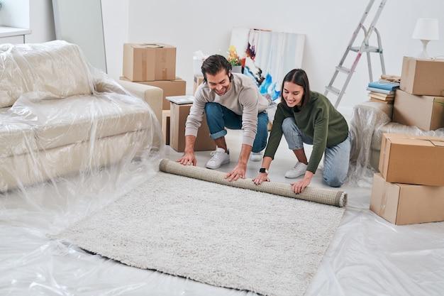 Счастливый молодой человек помогает своей жене свернуть ковер при подготовке гостиной своего нового дома или квартиры к ремонту после удаления