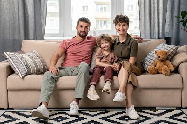 幸せな若い男、彼のかわいい妻と彼らのかわいい幼い息子は、窓のあるリビングルームのソファに座ってカジュアルウェアを着ています