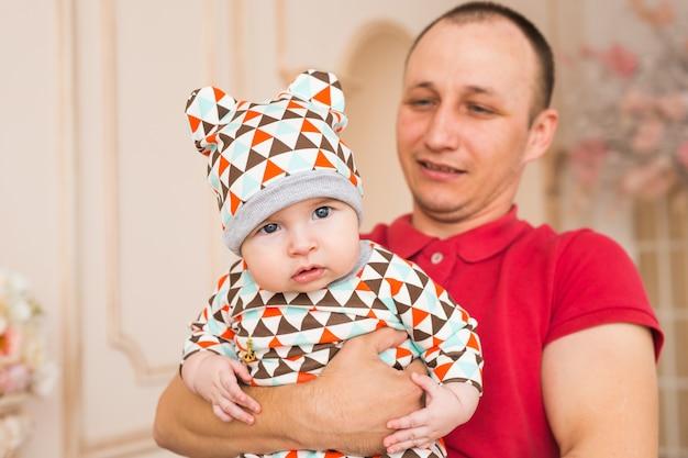 Счастливый молодой человек, держащий улыбающегося ребенка 4-5 месяцев, изолированного на белом