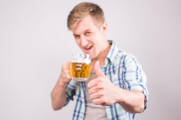 ビール ジョッキを押しながら親指を現して幸せな若い男。