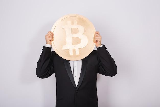 ピンクに大きな金色のビットコインを保持している幸せな若い男